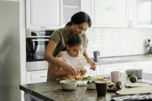 mother teaching her child how to cook